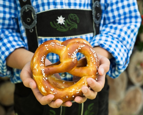 Close up of pretzel in the boy hands wearing a traditional bavarian clothes during Oktoberfest in Fredericksburg TX